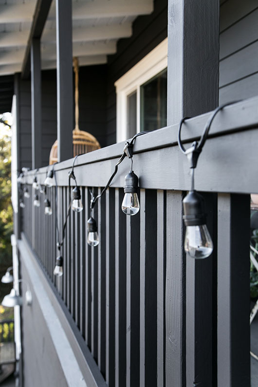 black house and porch with industrial string lights / sfgirlbybay
