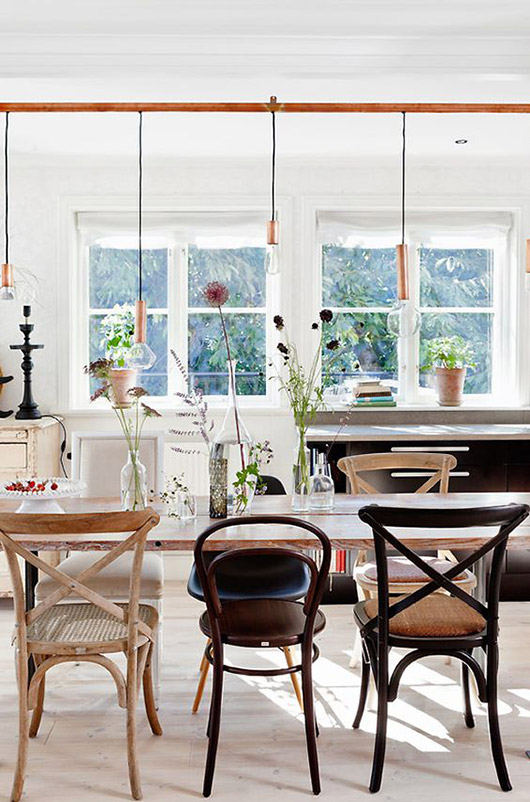 mismatched chairs around a rustic modern table with hanging lights / sfgirlbybay