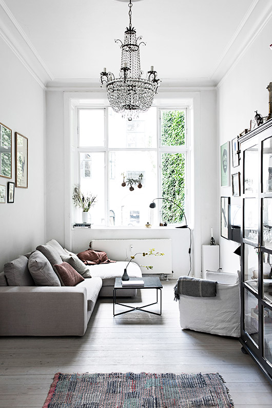 danish living room with modern gray sofa, black cabinet and chandelier / sfgirlbybay
