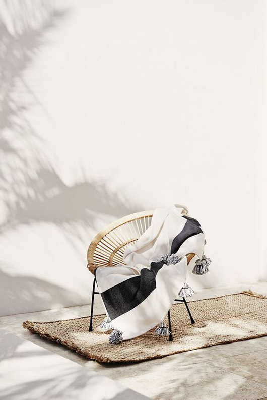 sisal rug under neutral acapulco chair with black and white throw blanket / sfgirlbybay