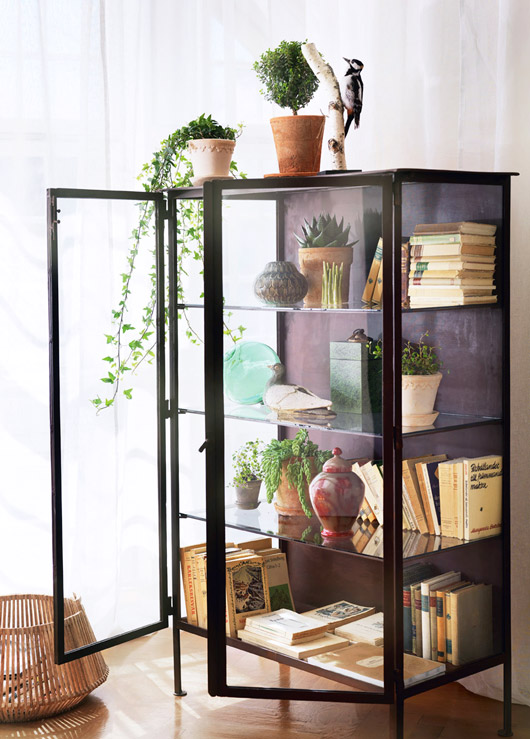 glass and black metal cabinet decorated with books and plants / sfgirlbybay