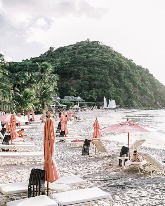 pink umbrellas on a sandy beach in st. lucia. / sfgirlbybay